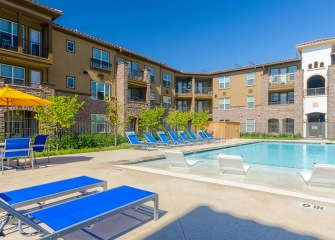 Villas Central Park pool with lounge chairs and landscaping