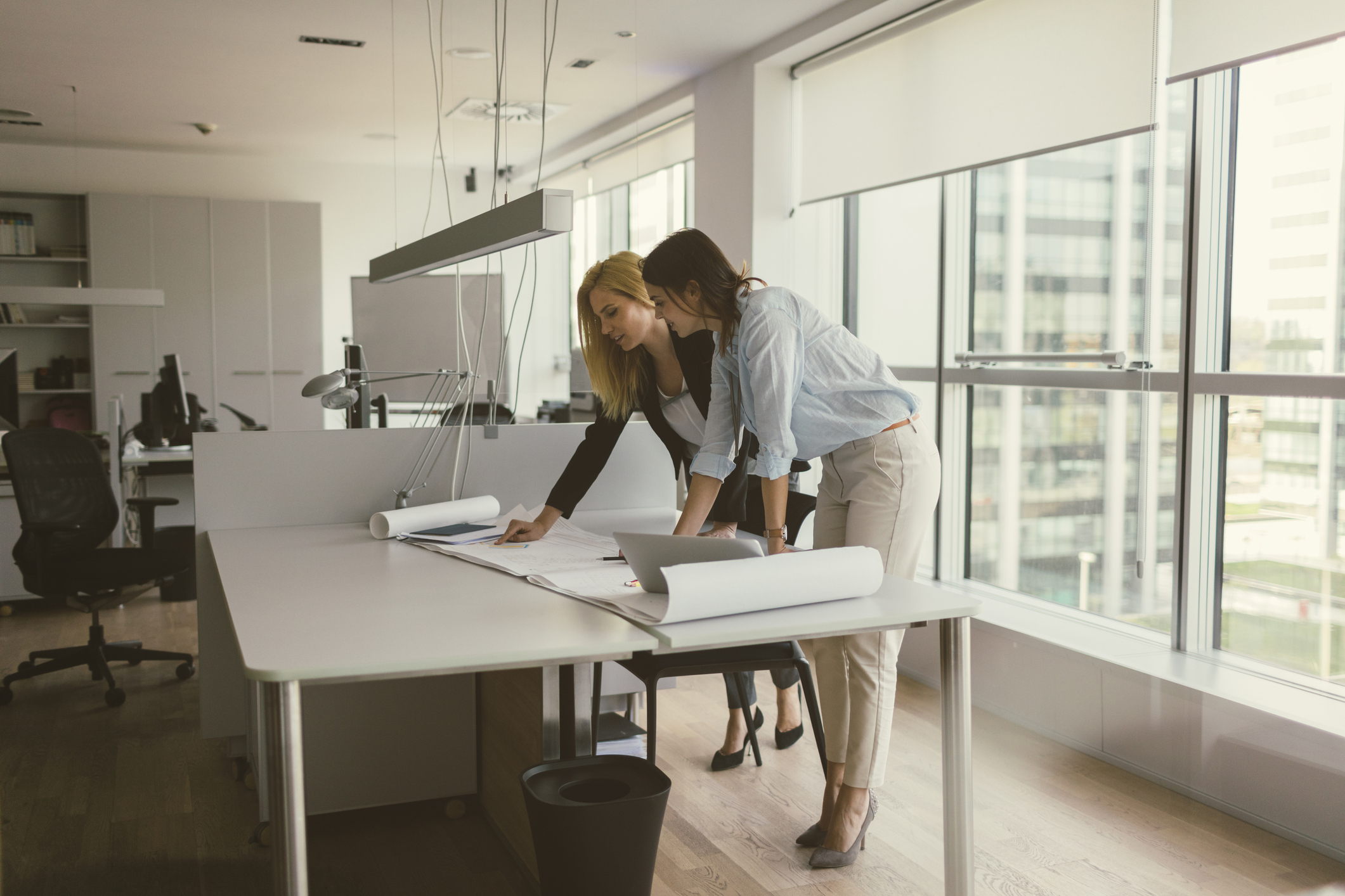 Two women looking over architectural plans in a spacious modern urban office